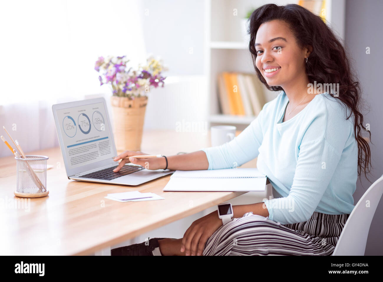 Cheerful smiling woman sitting at the table - Stock Image