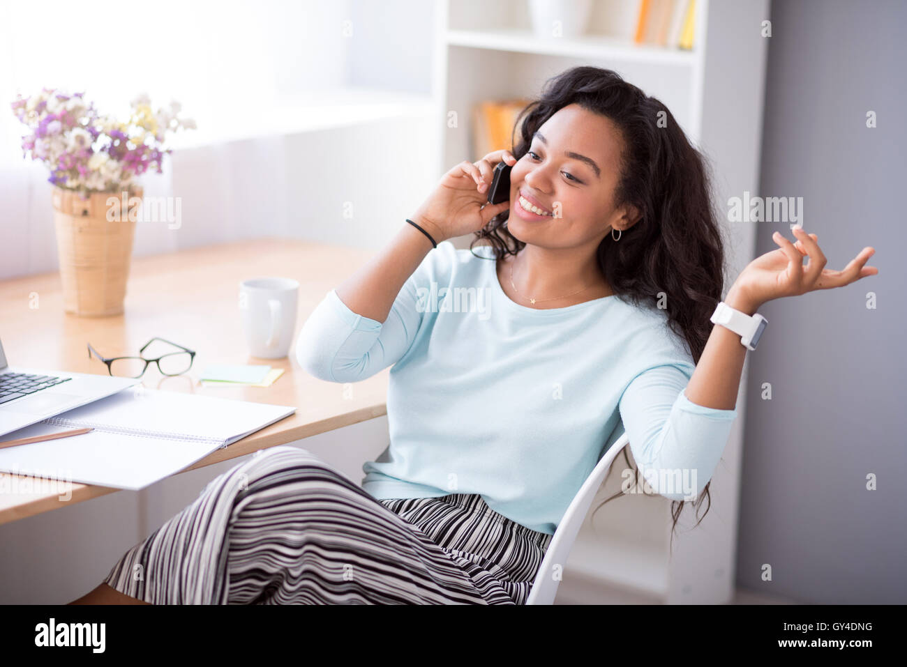 Positive woman talking on cell phone - Stock Image