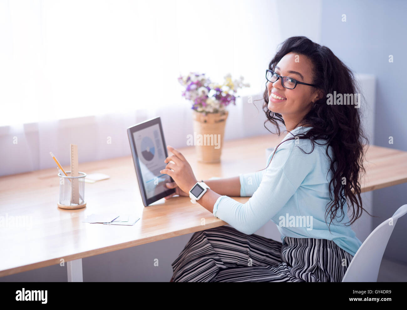 Positive woman sitting at the table - Stock Image