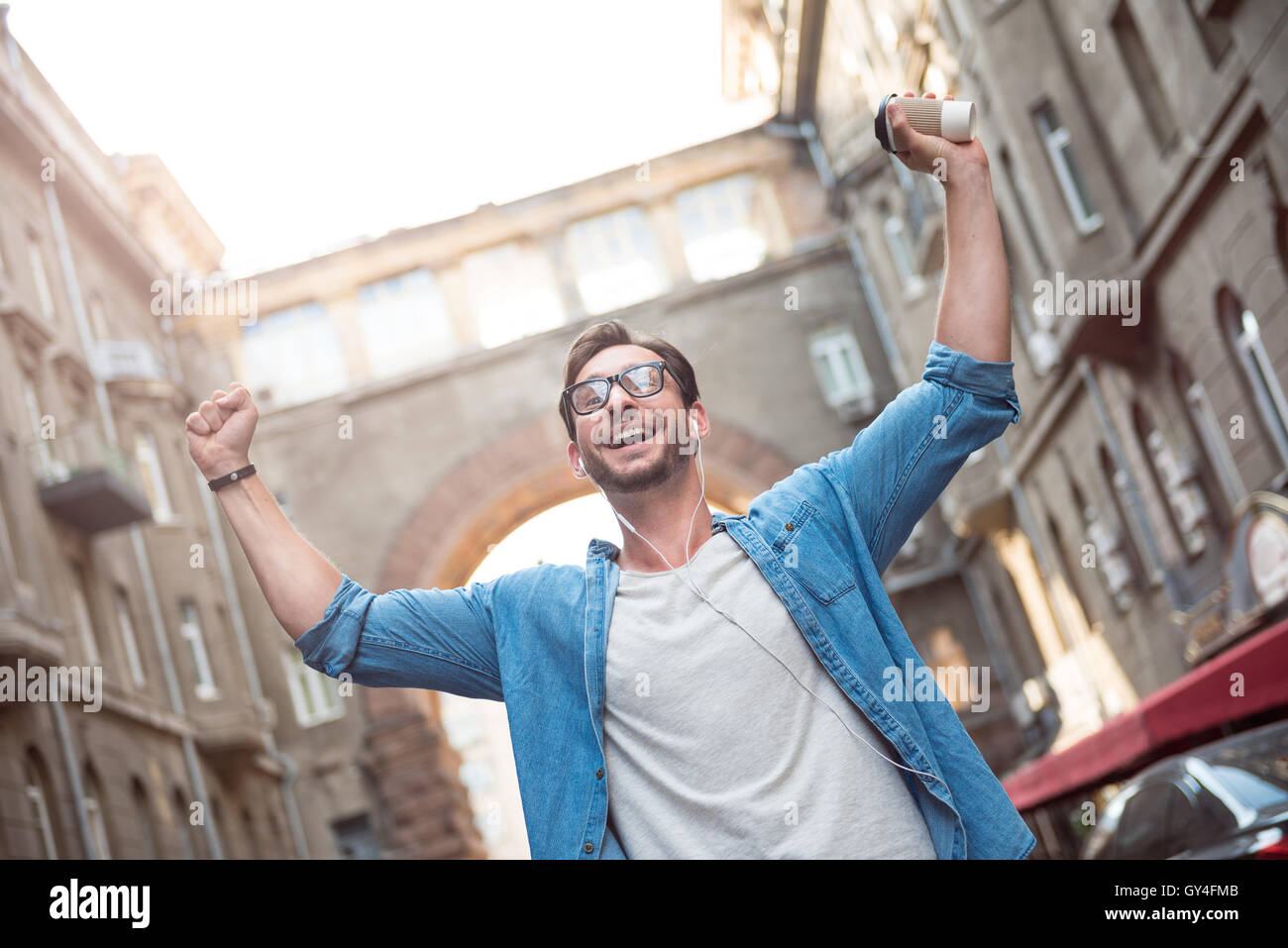 Happy man holding his hands up - Stock Image