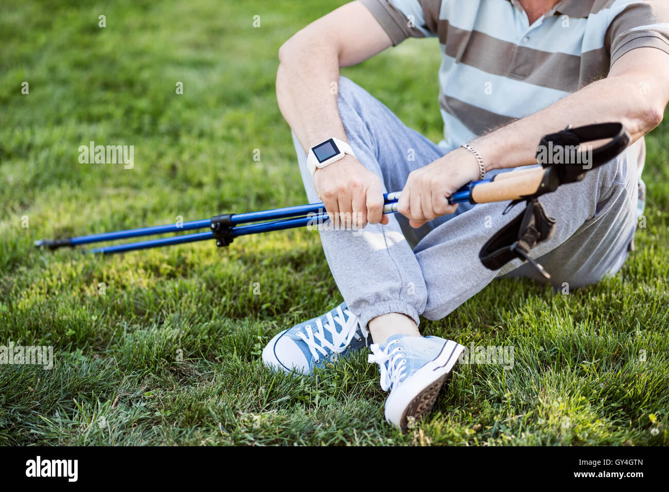 Man having rest after work-out on the grass - Stock Image