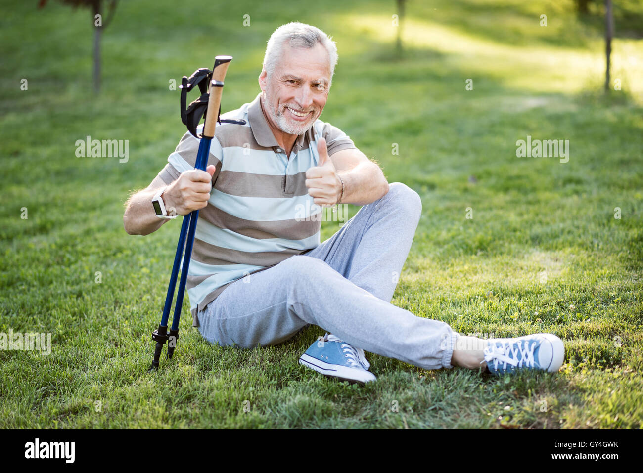 Good-looking old man sitting on grass with his legs crossed - Stock Image