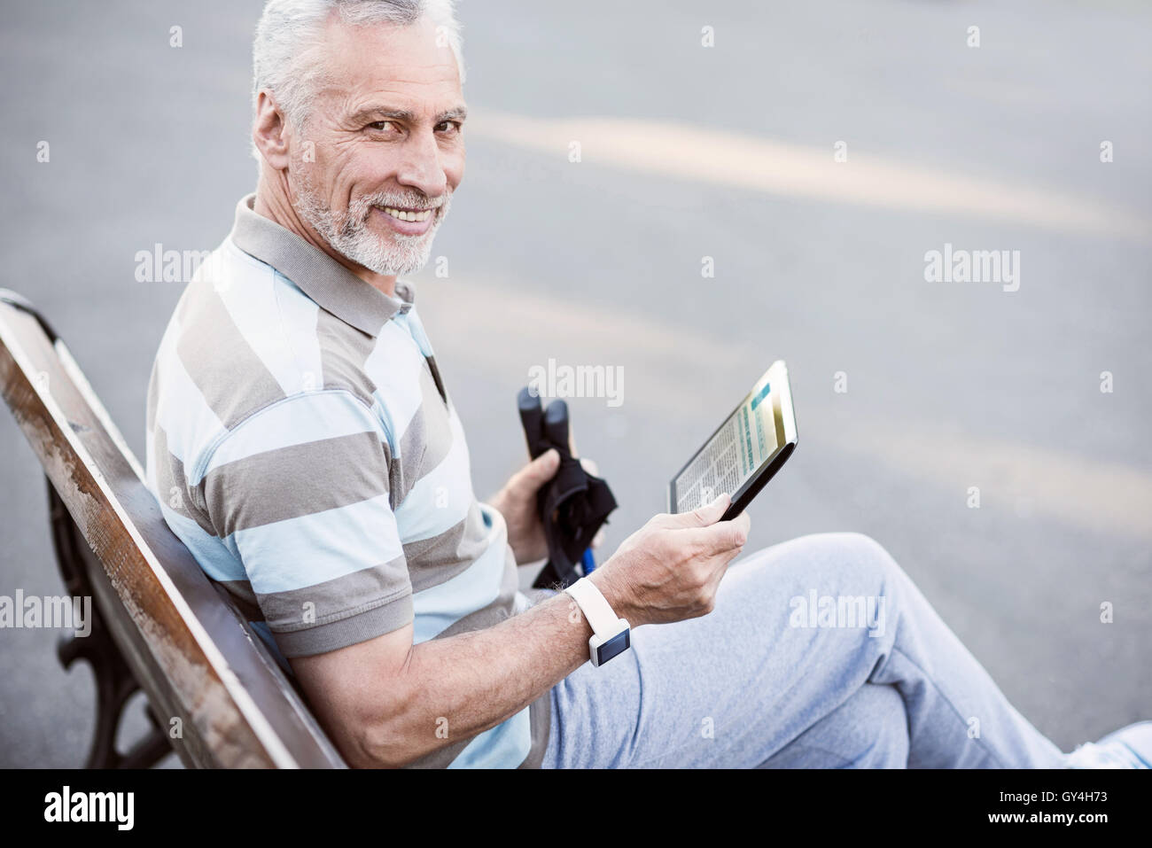 Sporty old man reading after the work-out in the park - Stock Image