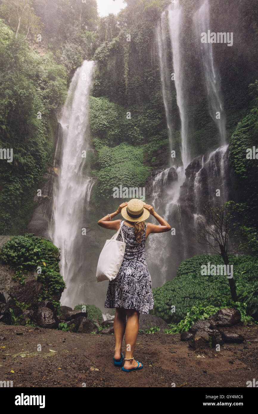 Rear view shot of female tourist admiring beautiful waterfall in tropical rain forest. Young woman looking at waterfall. - Stock Image