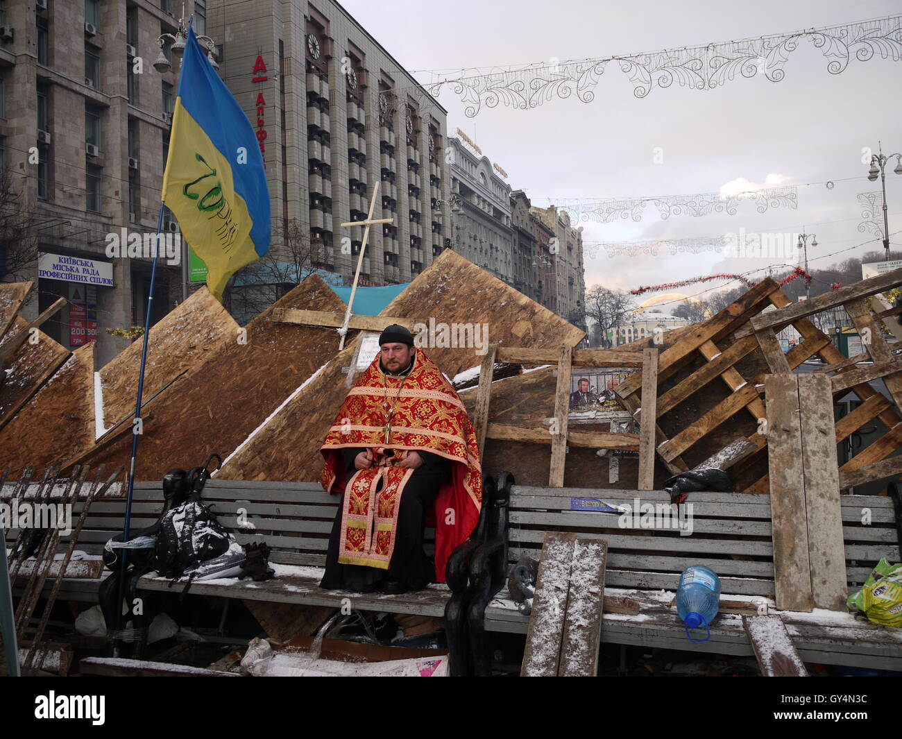 A Greek Catholic priest guard a barricade during the protets of winter 2013 in Kiev - Stock Image
