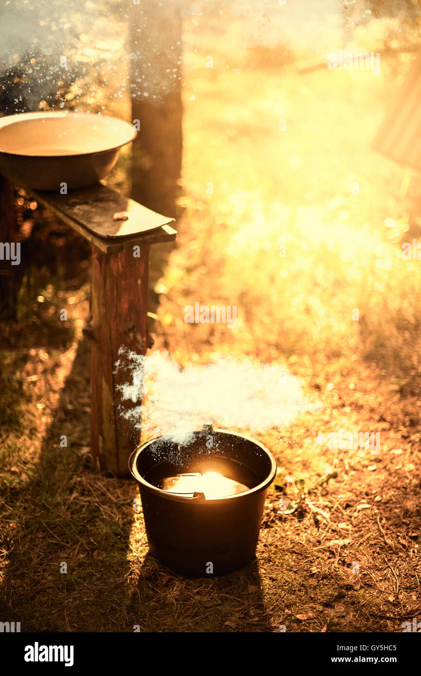 camping in the forest with a bench bawl and bucket with water inside - Stock Image