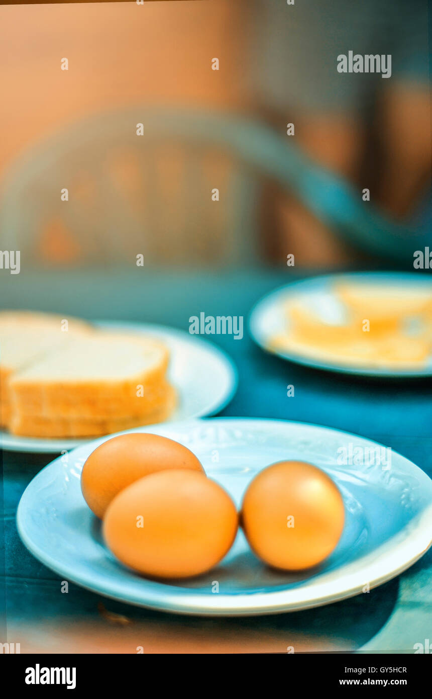 summer breakfast with three eggs and bread - Stock Image
