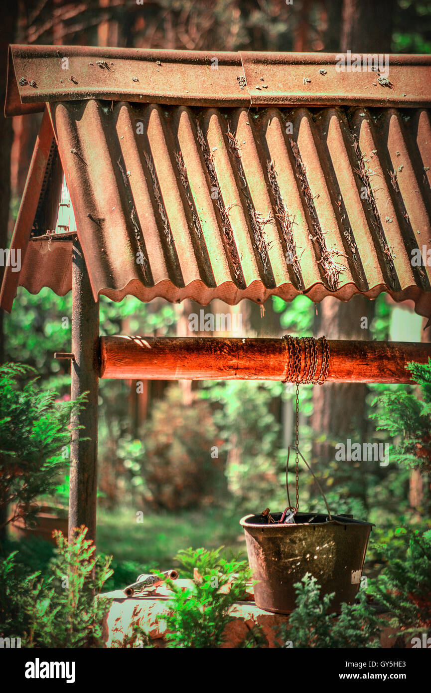 old wooden well in the middle of the forest Stock Photo