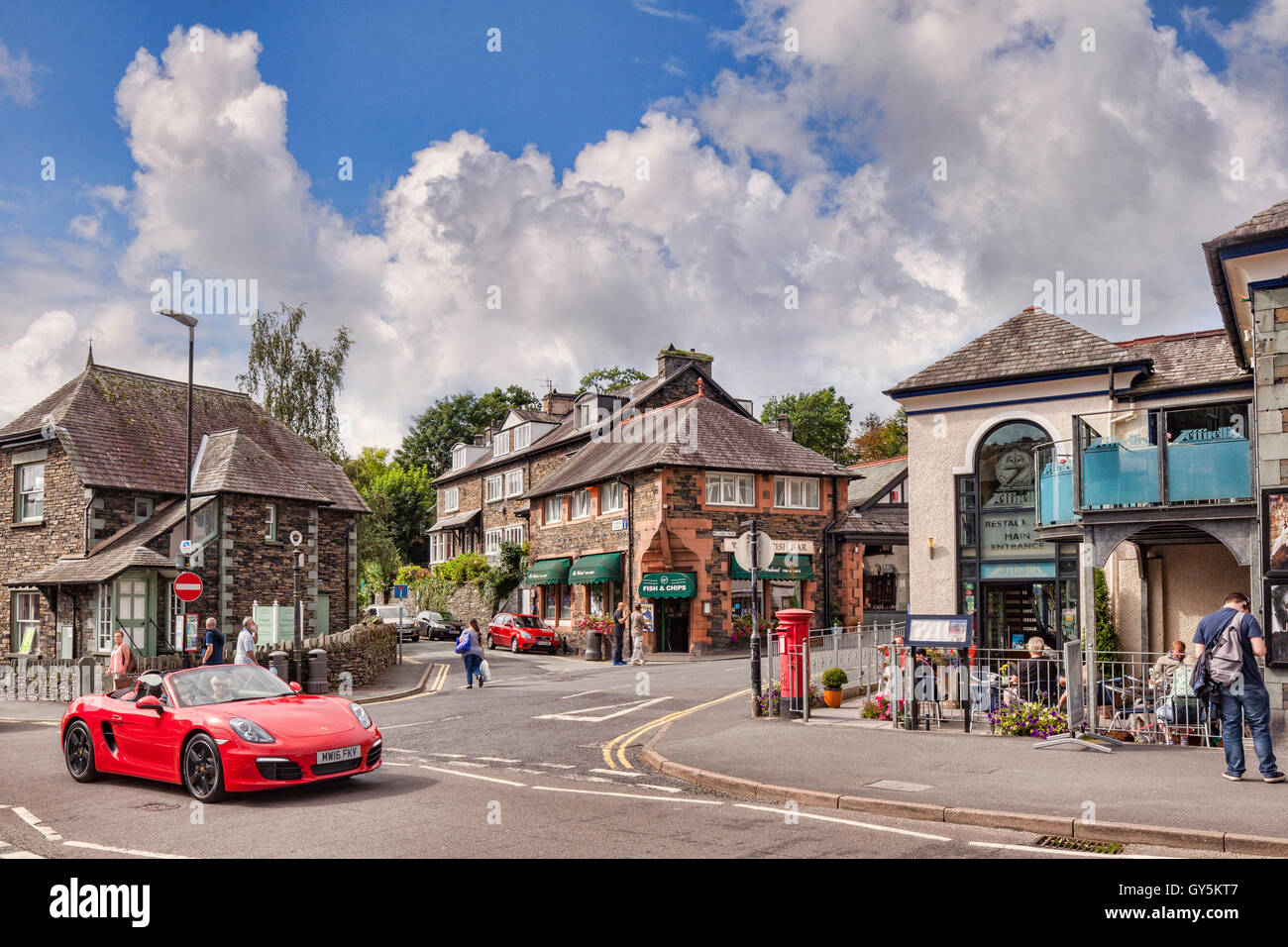 A red sports car driving through the village of Ambleside, Lake District National Park, Cumbria, England, UK - Stock Image