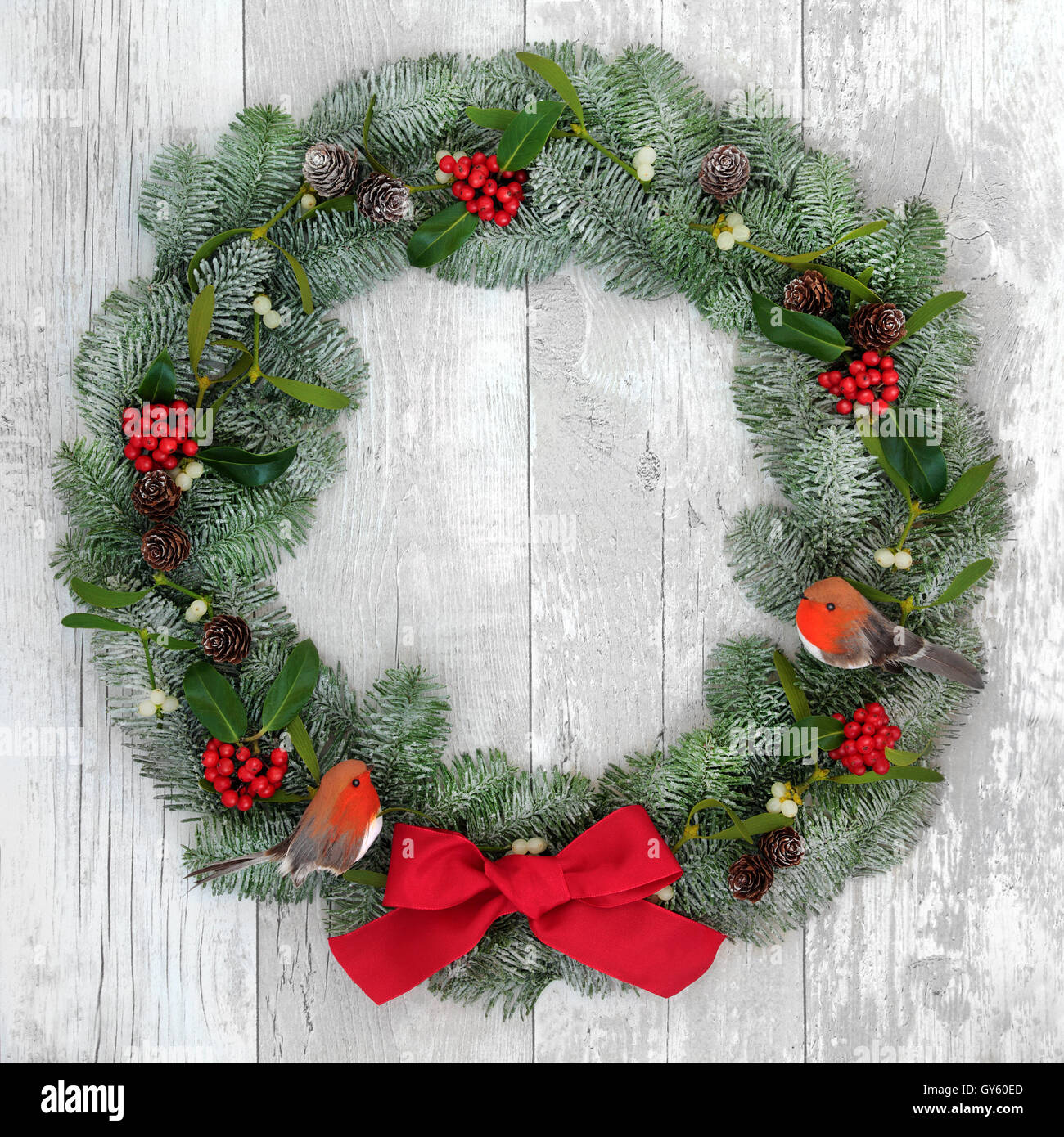 christmas wreath with robin decorations red bow holly mistletoe and snow covered blue spruce fir over distressed white wood