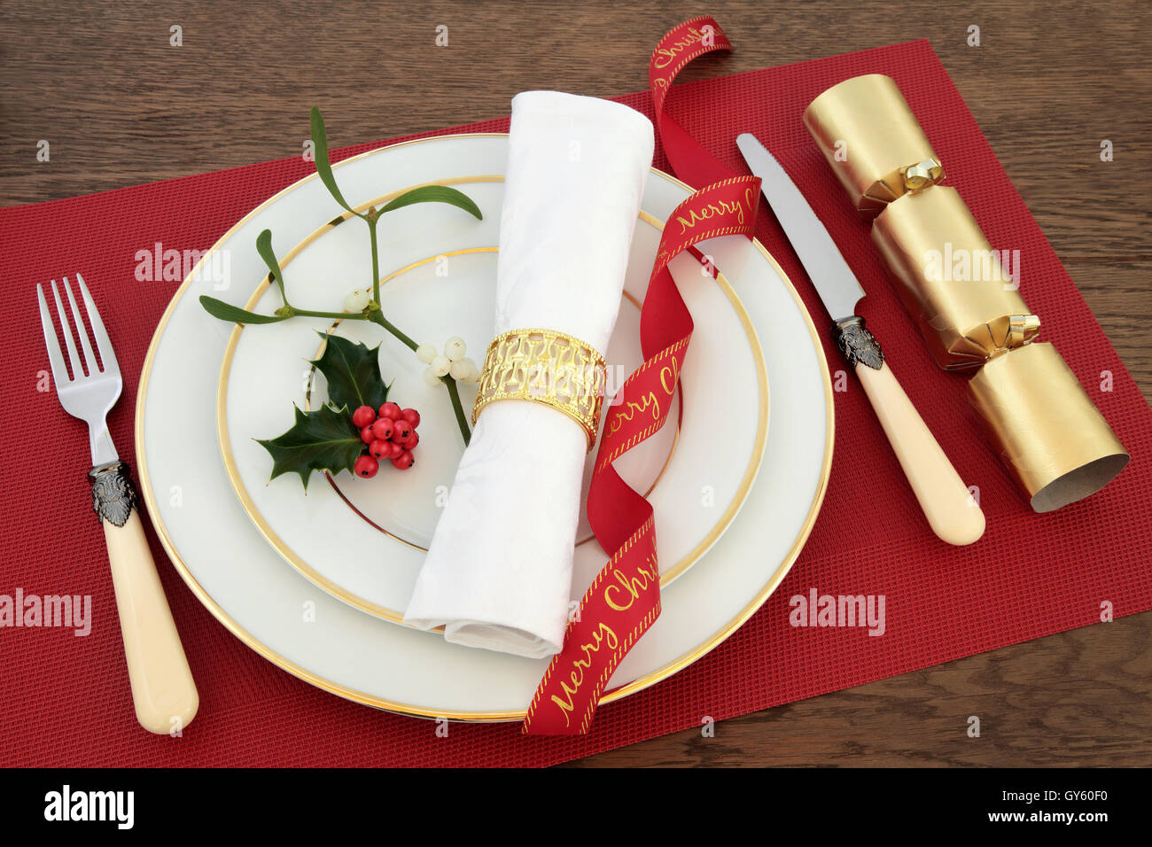 Christmas dinner table setting with white plates, knife and fork ...