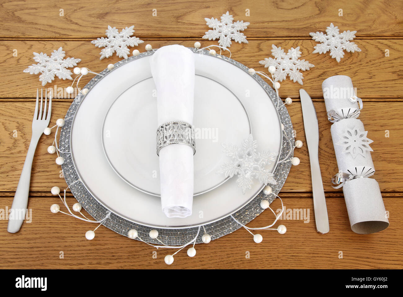 Christmas dinner table setting with white porcelain plates cutlery linen serviette with napkin ring and snowflake baubles & Christmas dinner table setting with white porcelain plates cutlery ...