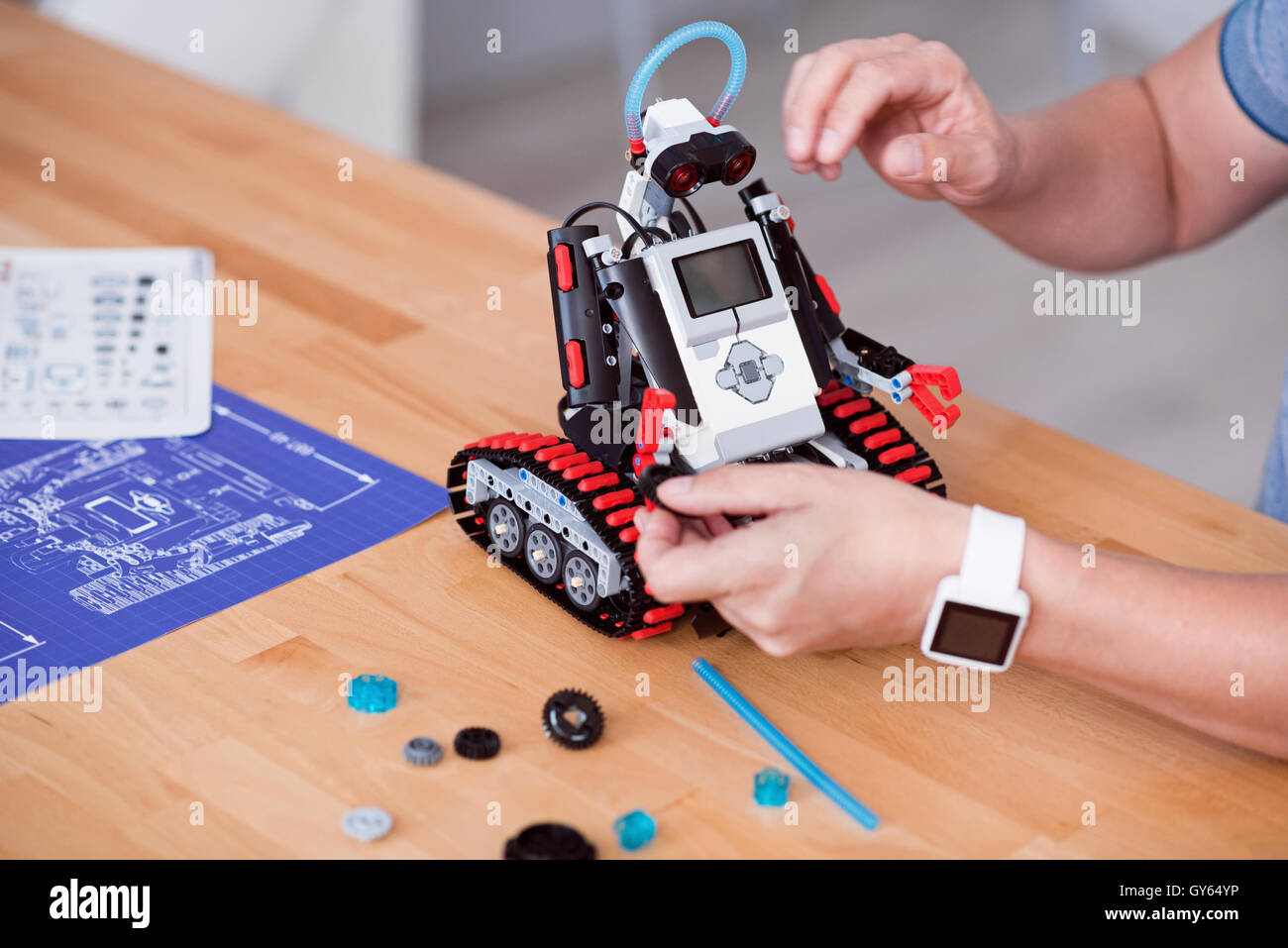 Pleasant man constructing robot - Stock Image