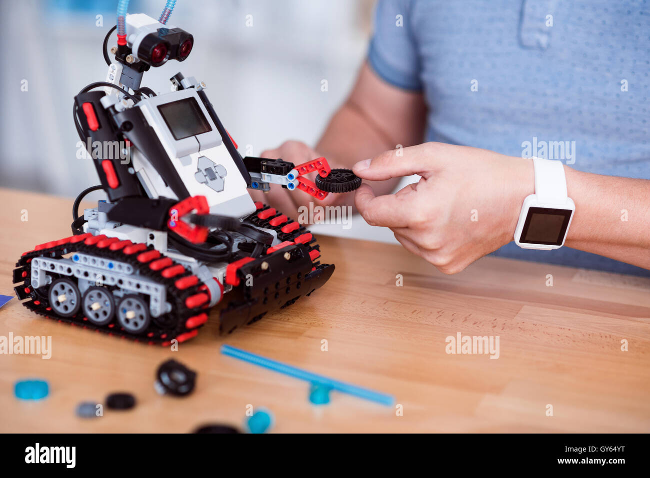 Pleasant man constructing robot. - Stock Image