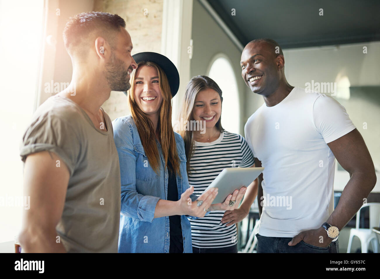 Successful young business team of enthusiastic modern young people in informal clothing standing in the office having - Stock Image