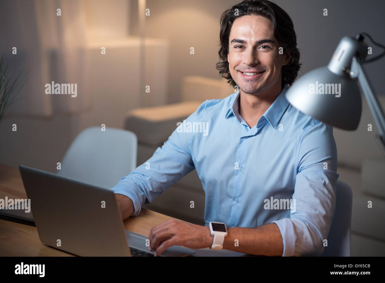 Handsome smiling man working on laptop. - Stock Image