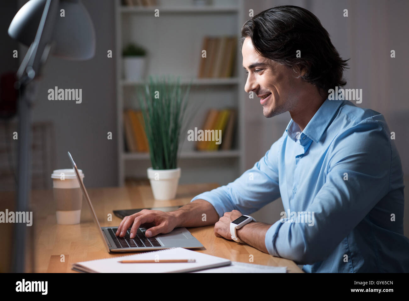 Good looking man working on laptop. - Stock Image
