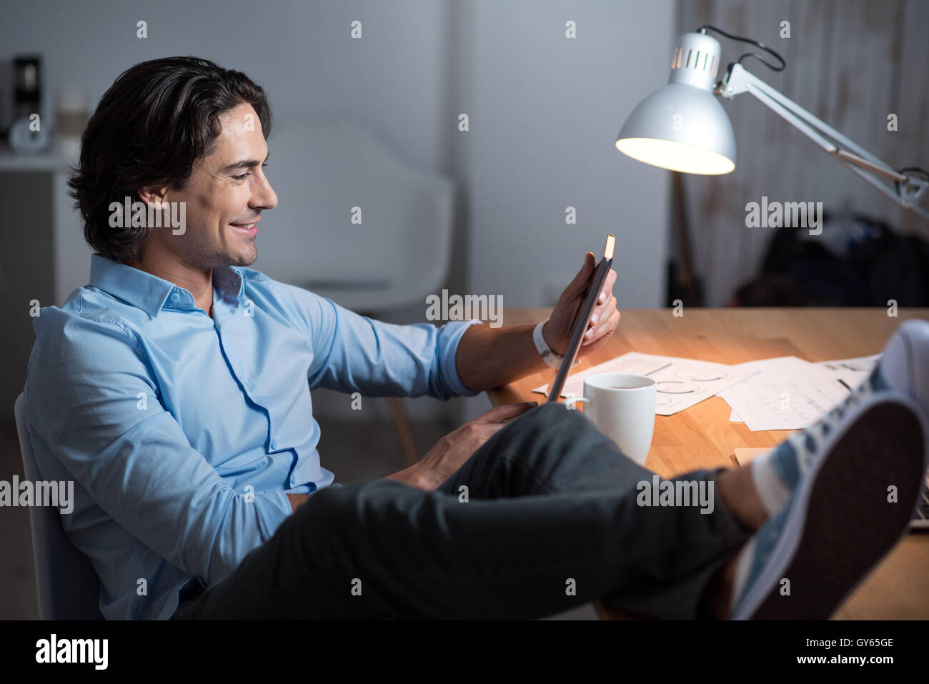 Handsome cheerful yang man using tablet. - Stock Image