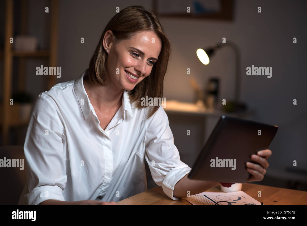 Joyful woman sitting at the table - Stock Image