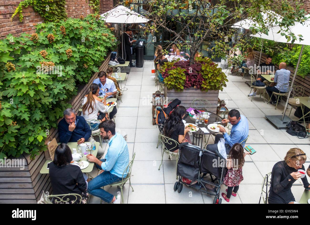 Diners enjoying a garden restaurant setting in Lower Manhattan - Stock Image