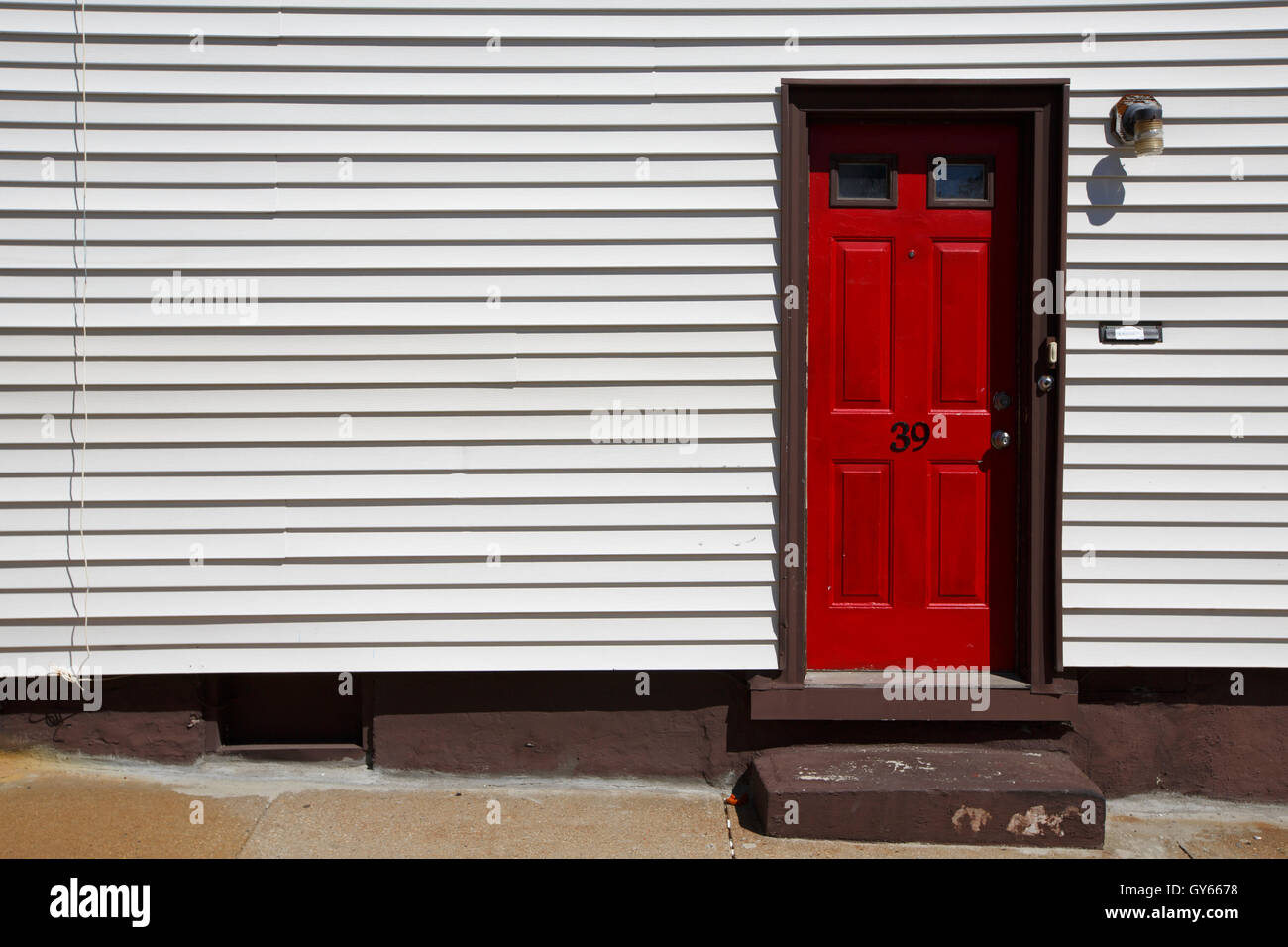 Red door, vinyl siding, Boston, Massachusetts - Stock Image