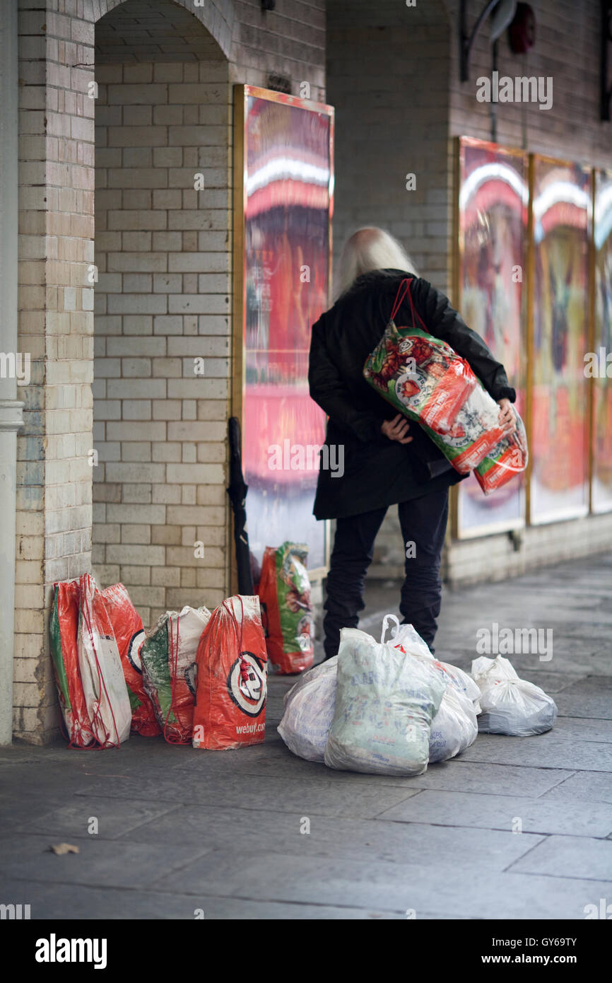 Homeless man with his carrier bags on the streets of London - Stock Image