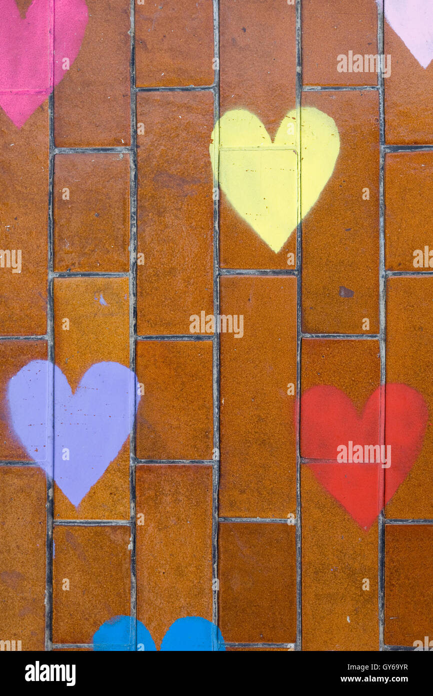 Colorful hearts painted on a brick pattern - Stock Image