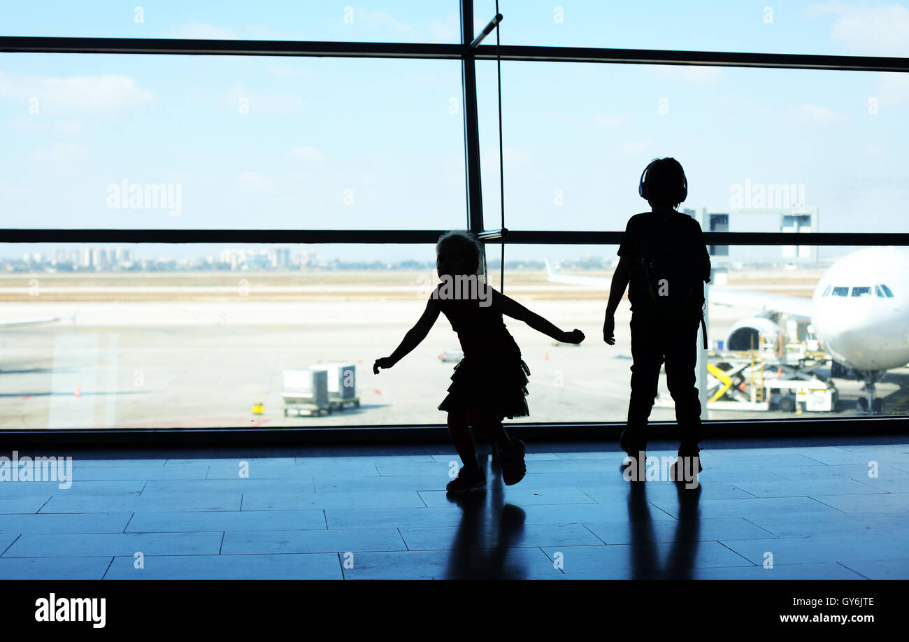 Silhouette of two kids standing in front of the window in airport Stock Photo