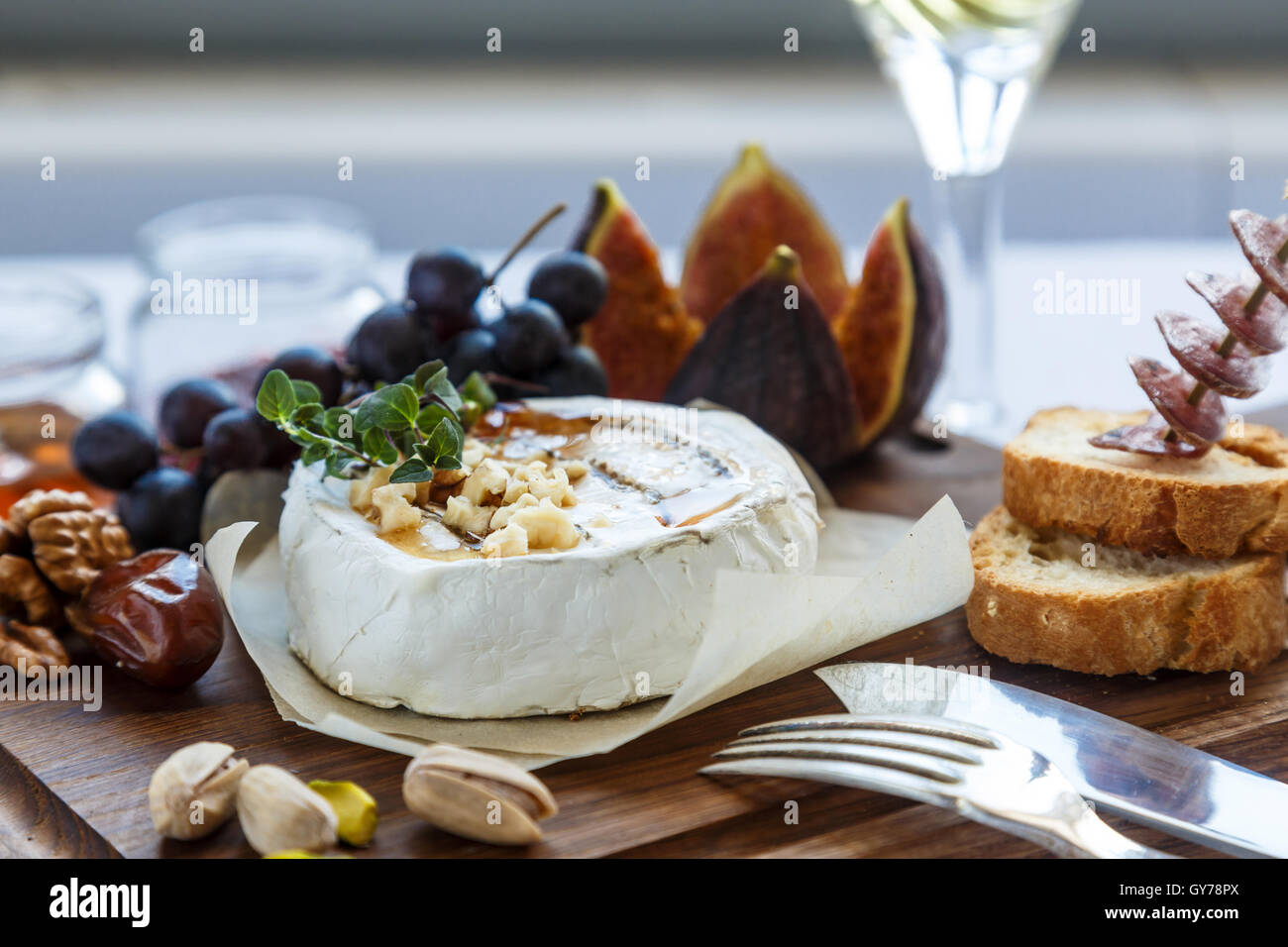 Baked camembert cheese with figs, honey, grapes and nuts. Top view - Stock Image