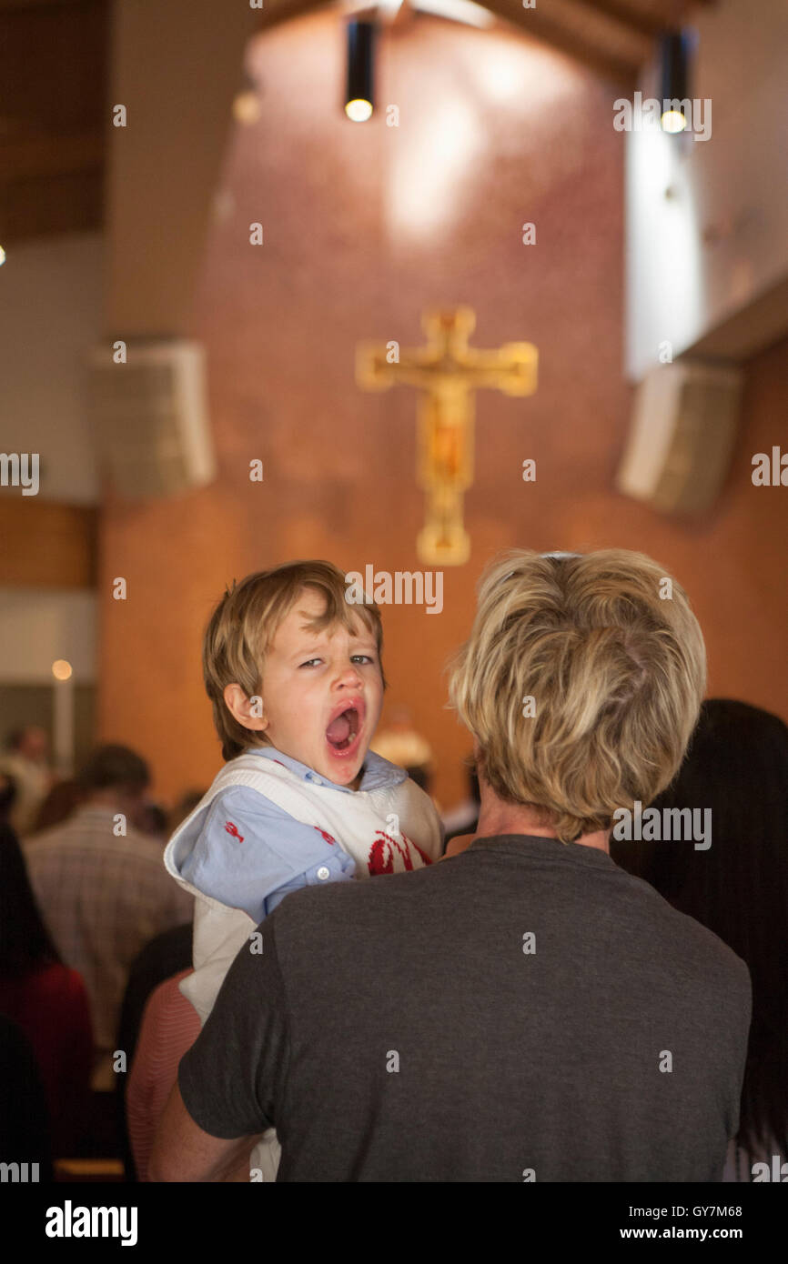 A four year old boy yawns with boredom on his father's shoulder during mass at a Laguna Niguel, CA, Catholic - Stock Image