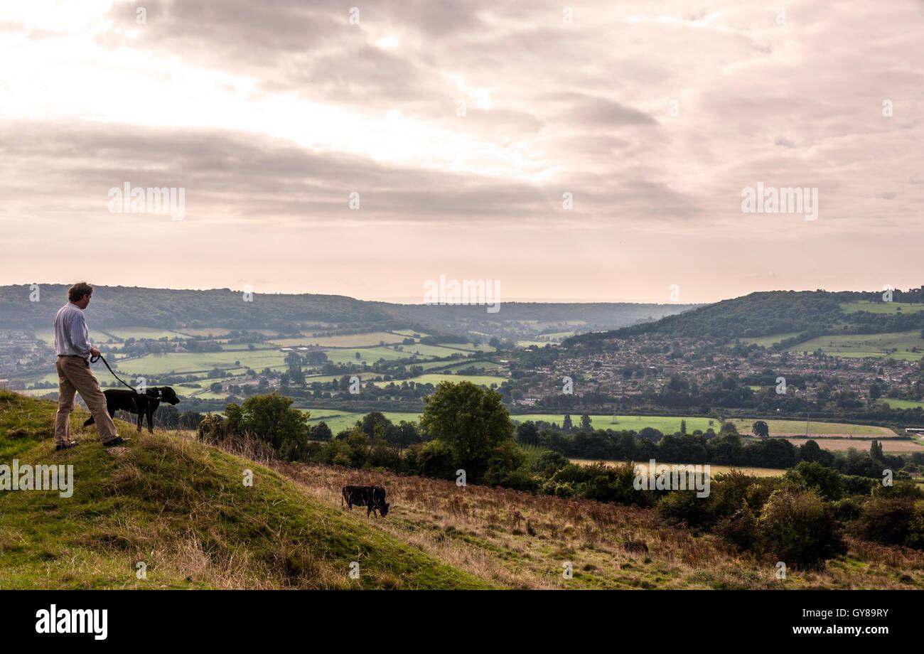 Little Solsbury Hill, Batheaston, Somerset, UK. 18th Sept, 2016. A dog walker looks out over Bathampton water meadows Stock Photo