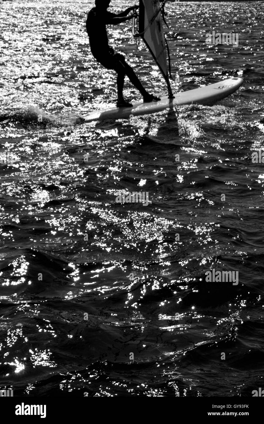 Black & White photograph of a windsurfer on windsurfing board on the sea,  the windsurfer is silhouetted against - Stock Image