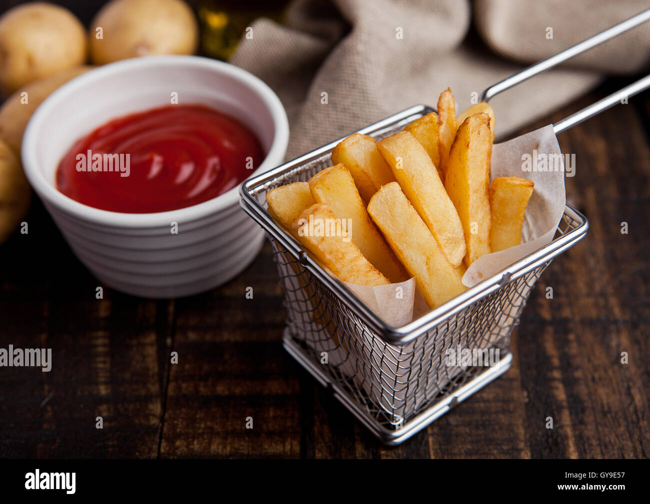 Fried french fries chips in fryer with ketchup on wood - Stock Image