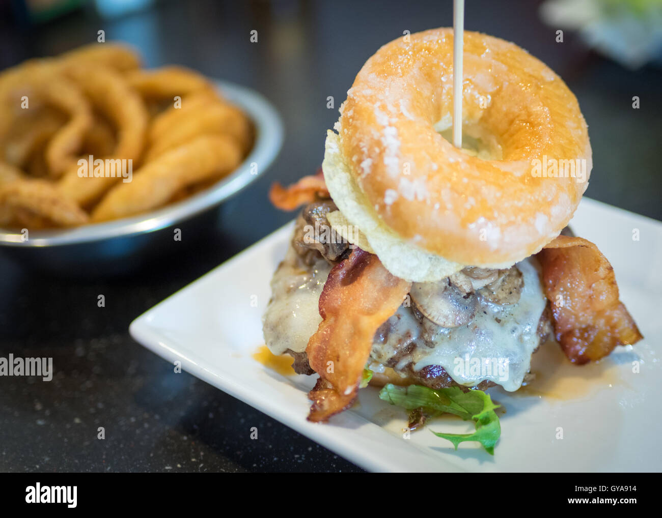 A bacon donut burger (Luther Burger) from Soda Jerks restaurant in Edmonton, Alberta, Canada. - Stock Image