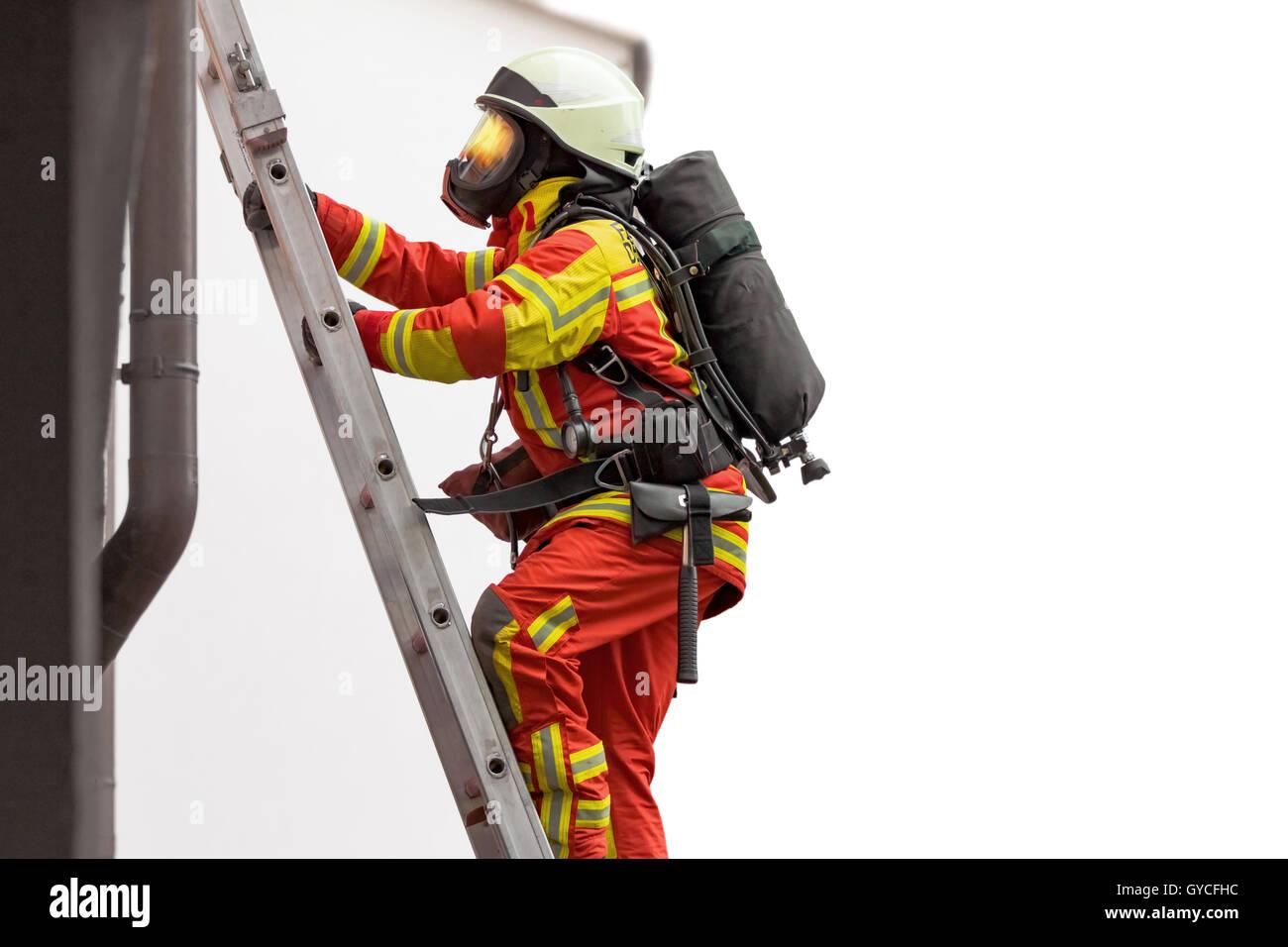 Fireman climbing a ladder set on a building - Stock Image