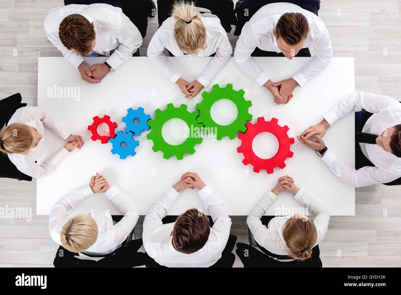 Business team sitting around the table with cogs, teamwork concept - Stock Image