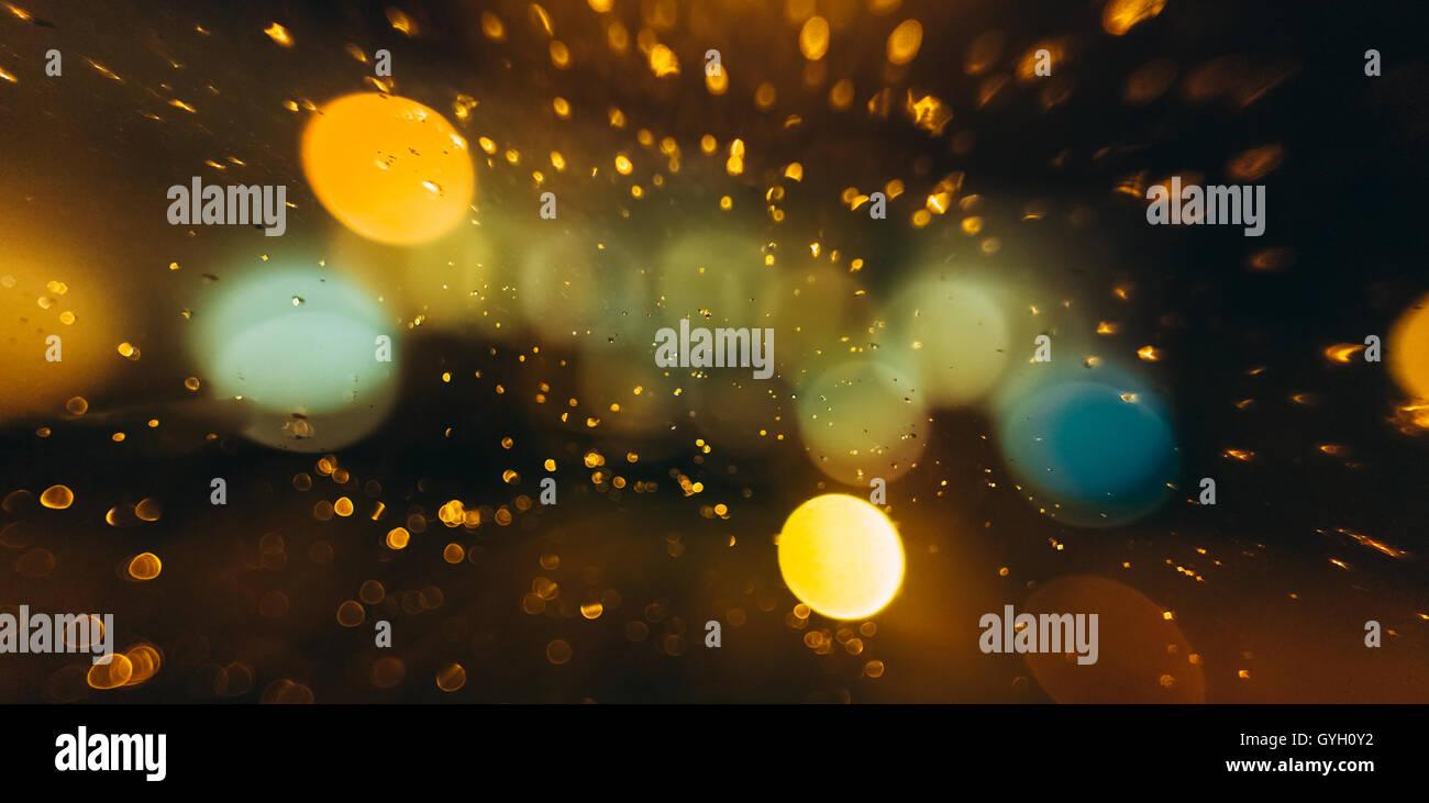 Glowing Lights On Unfocused Bokeh Blurred Dark Background. - Stock Image