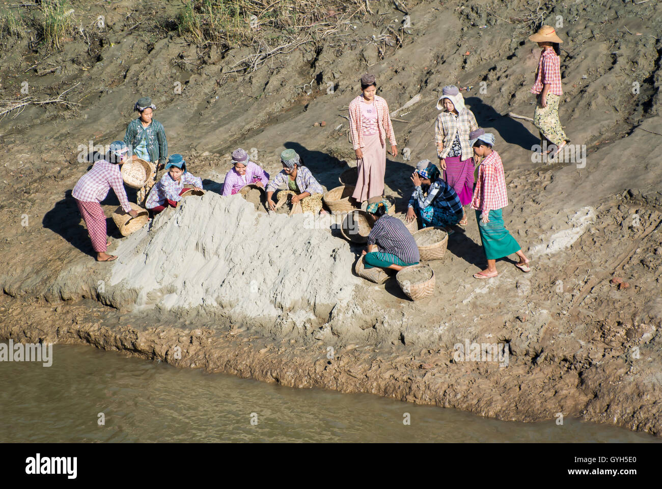 Village Women at Shoreline Collecting Clay to Make Pottery, Myanmar - Stock Image