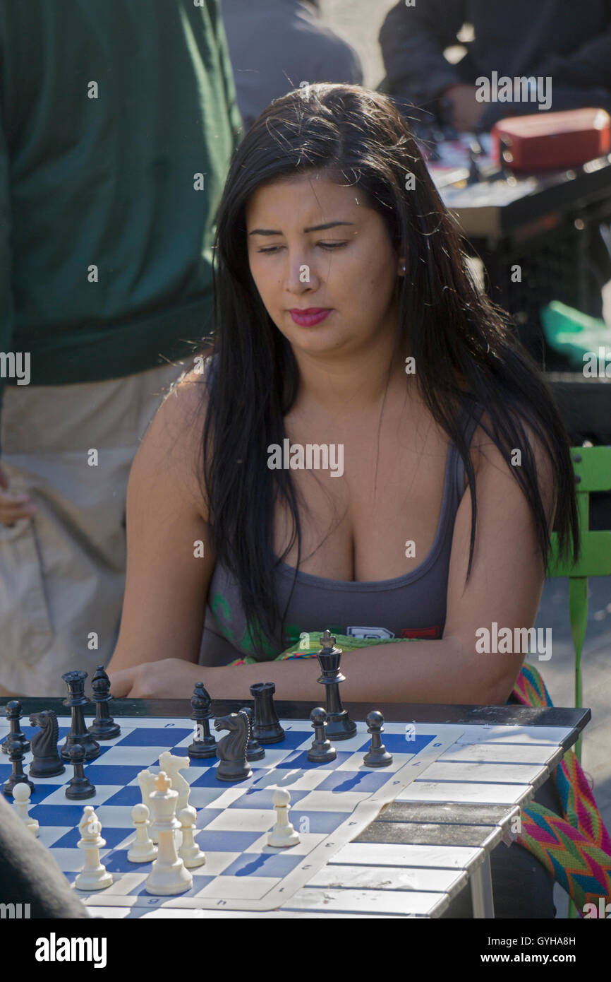 An attractive woman playing chess against a man at Union Square Park in Manhattan, New York City - Stock Image