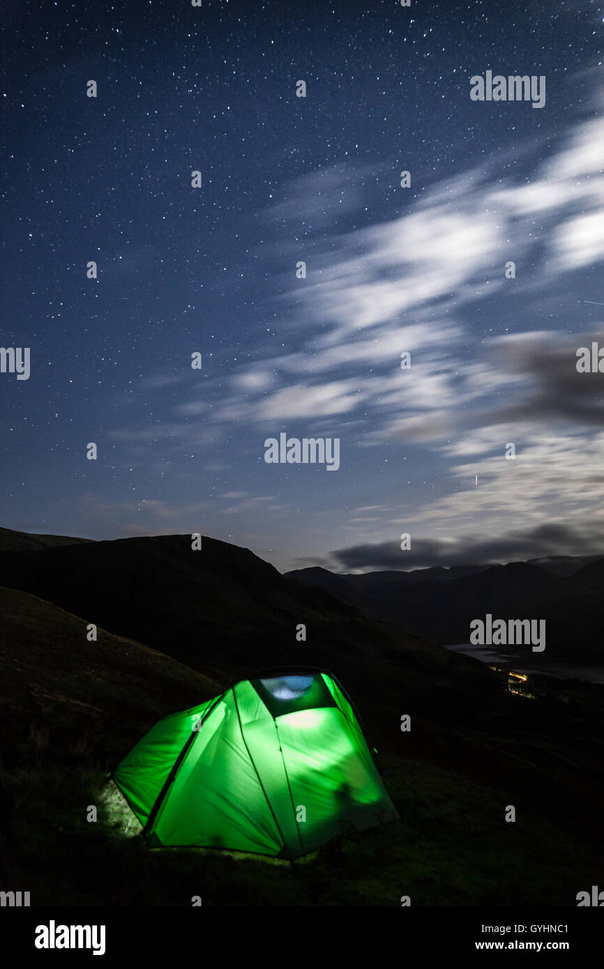Glowing tent from torch light, wild camping under a star filled sky on the fells above Buttermere in the English - Stock Image