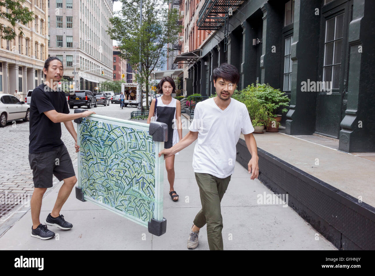 Lower Manhattan New York City NYC NY Tribeca Asian man woman painting framed carrying walking street scene young Stock Photo