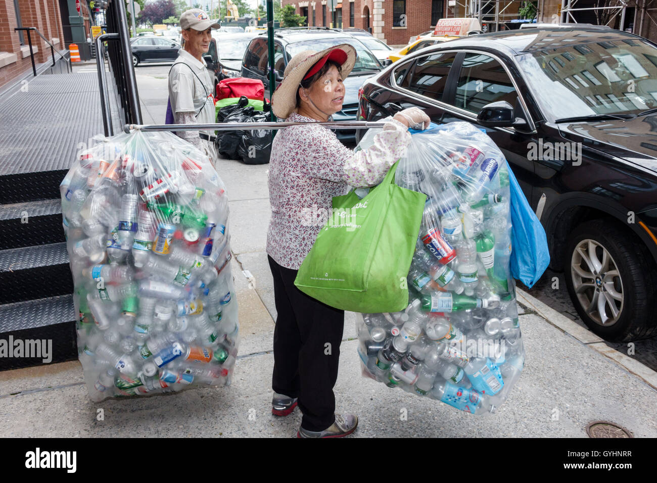 Lower Manhattan New York City NYC NY Tribeca Asian man woman mature recycling aluminum cans plastic bags carrying Stock Photo