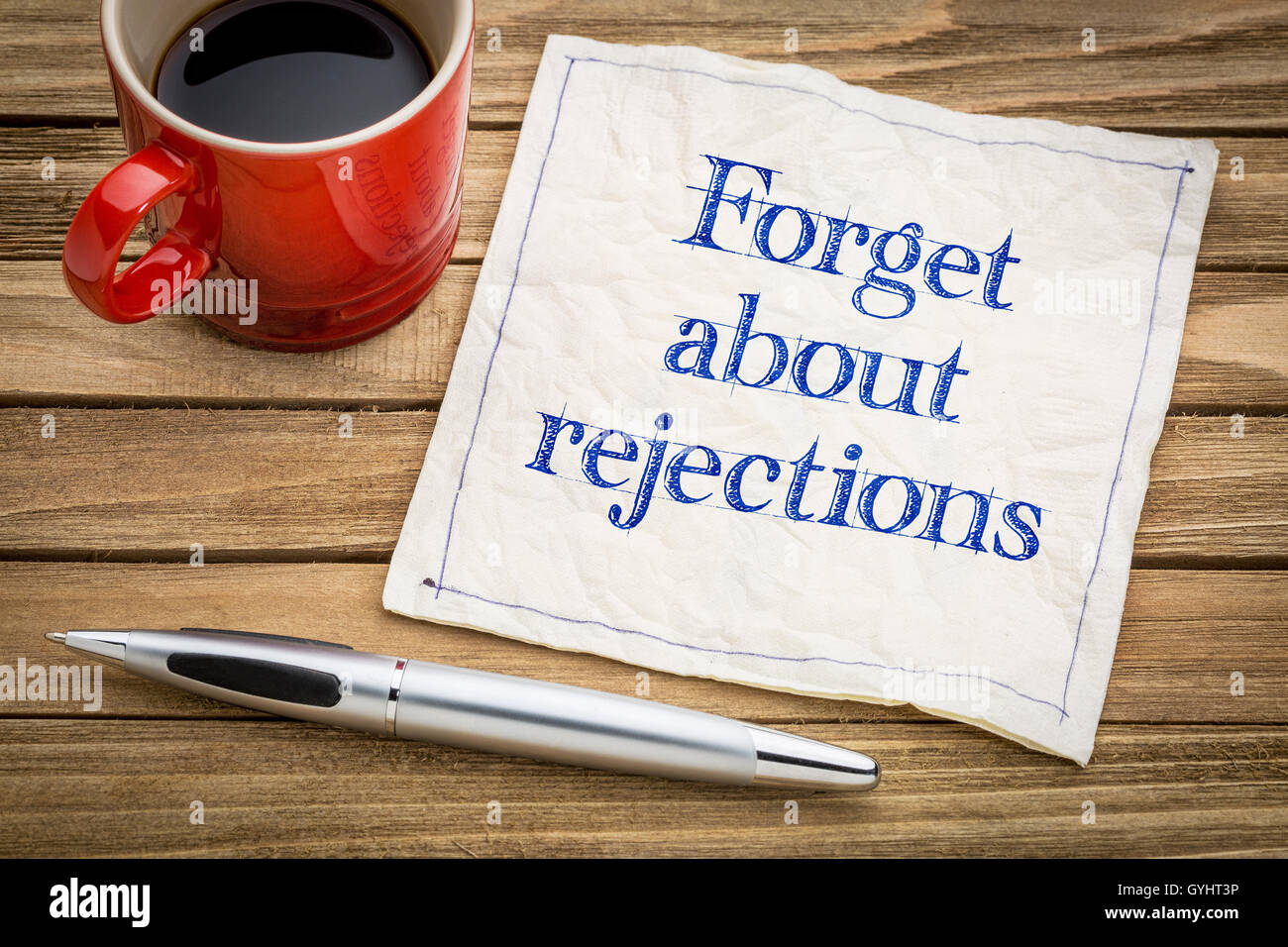 Forget about rejections - handwriting on a napkin with a cup of espresso coffee - Stock Image