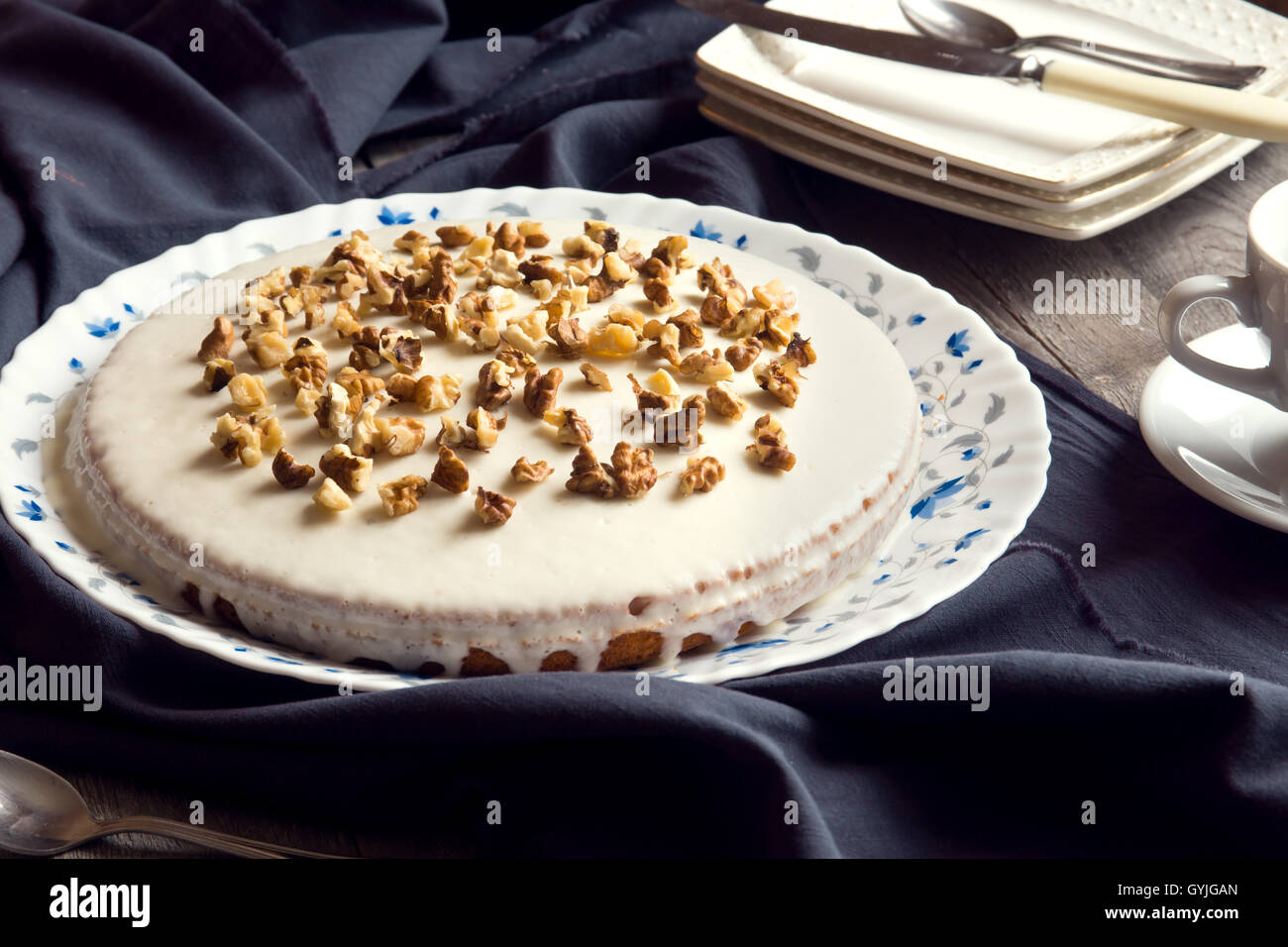 Homemade pumpkin and walnut cake with cream icing over rustic wooden table - healthy homemade pastry - Stock Image
