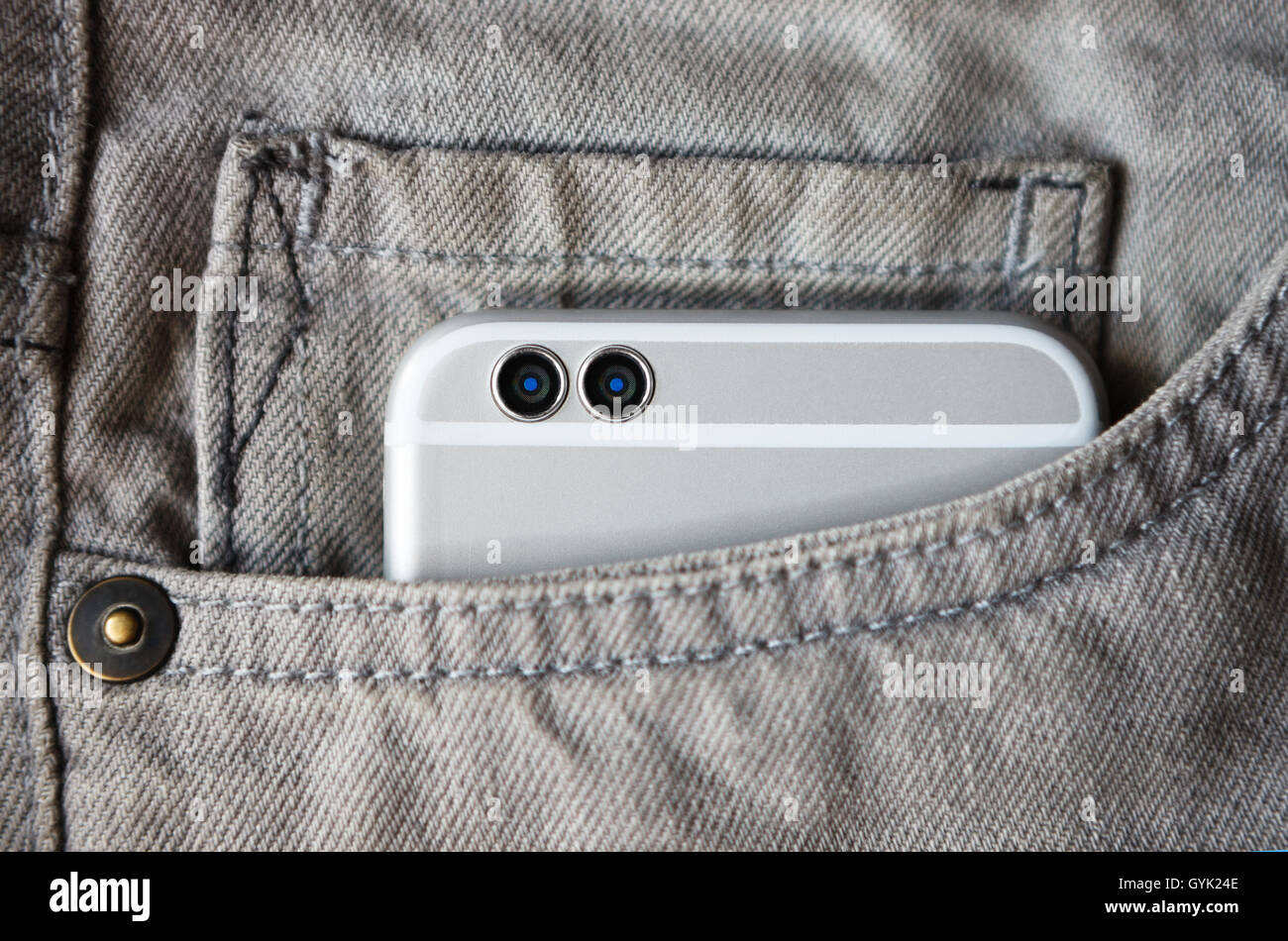 Modern 2d camera smart phone in jeans pocket. Silver gadget, grey trousers, horizontal orientation - Stock Image