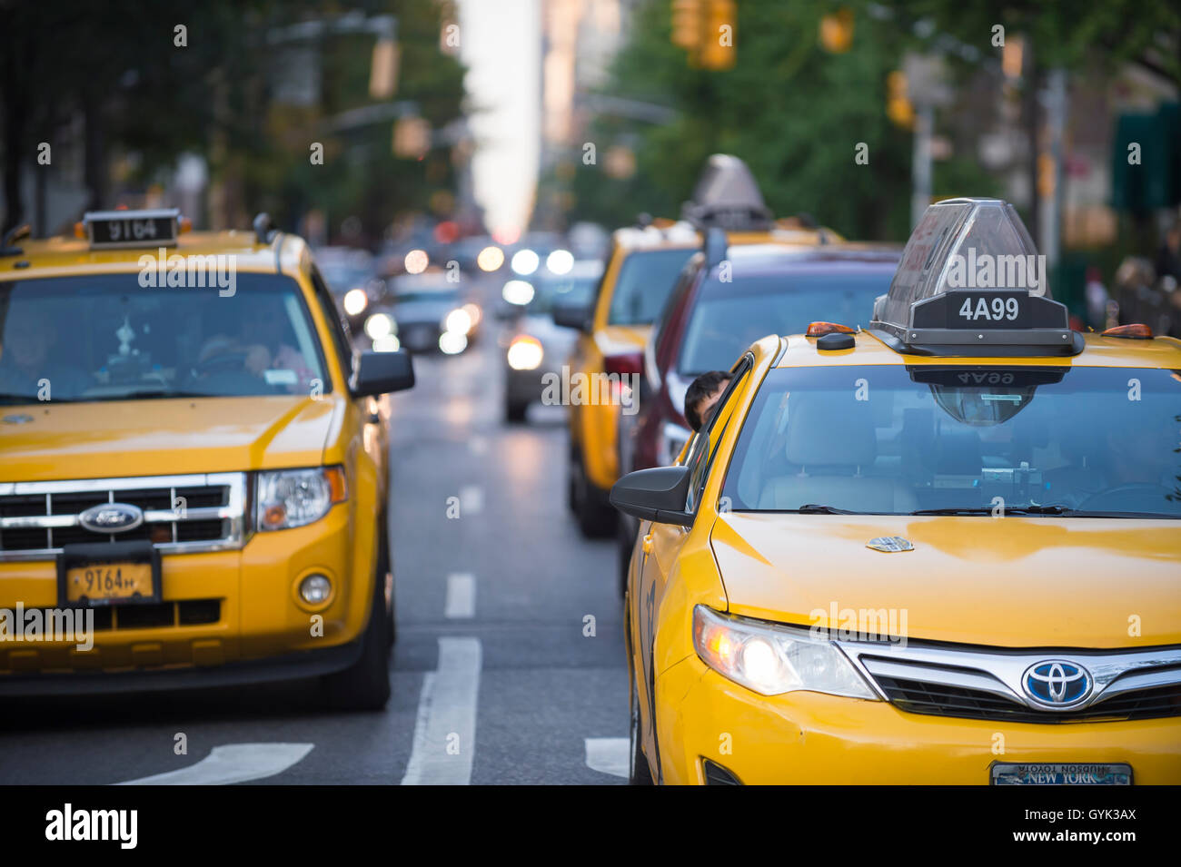 NEW YORK CITY - SEPTEMBER 4, 2016: Yellow taxis head downtown on a typical late afternoon scene on lower Fifth Avenue. Stock Photo
