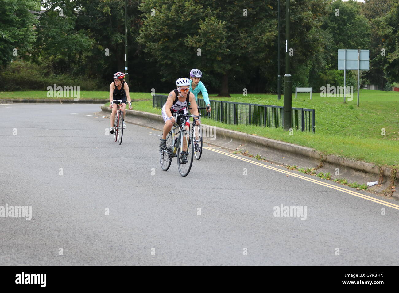 Three women triathletes during the cycling leg of the Crawley Triathlon. - Stock Image