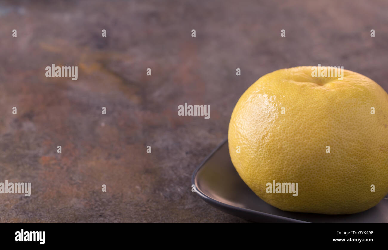 Sweetie on plate from right side of old background - Stock Image