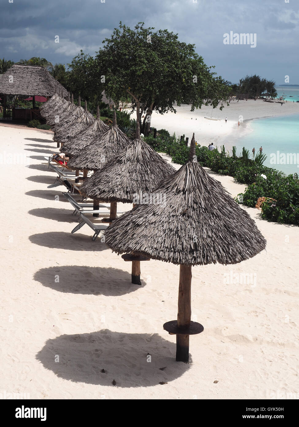 View looking down on a row of thatched sun shade umbrellas casting shadows on a white sandy beach Stock Photo