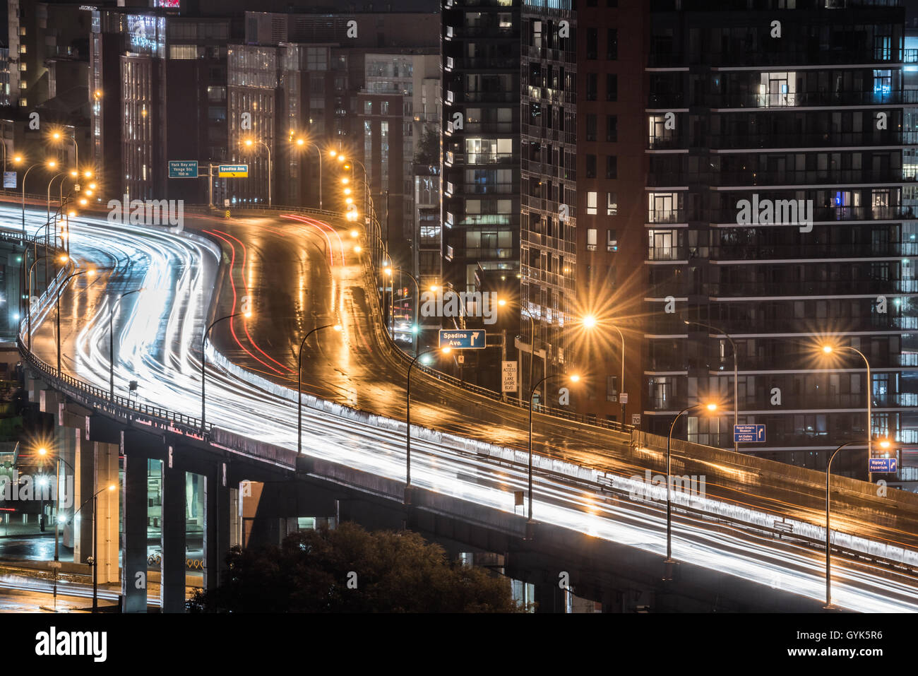 Glowing light streaks from a wet Gardiner Expressway as traffic never stops.  Hot & rainy summer night in Lakeside - Stock Image